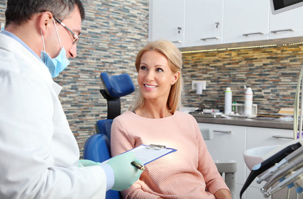 Woman smiling at dentist before getting sedation at Implant and Periodontal Wellness Center of Arizona in Phoenix, AZ